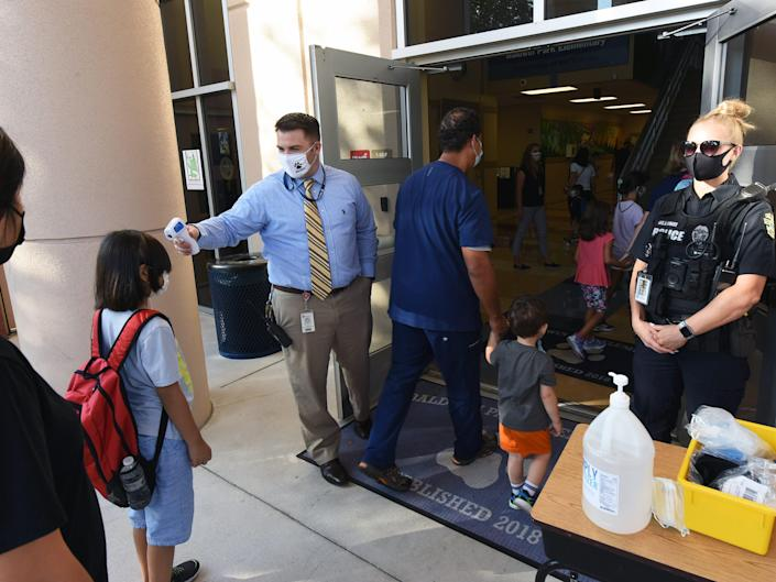 Principal Nathan Hay performs temperature checks on students as they arrive on the first day of classes for the 2021-22 school year at Baldwin Park Elementary School, August 10, 2021.