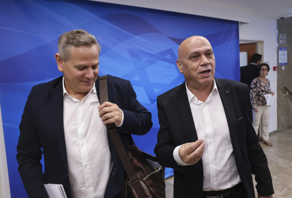 """Israeli Minister of Health Nitzan Horowitz, left, and Minister of Regional Cooperation Issawi Frej arrive for the first weekly cabinet meeting of the new government in Jerusalem, Sunday, June 20, 2021. Prime Minister Naftali Bennett opened his first Cabinet meeting on Sunday since swearing in his new coalition government with a condemnation of the newly elected Iranian president, whom he called """"the hangman of Tehran."""" (Emmanuel Dunand/Pool Photo via AP)"""