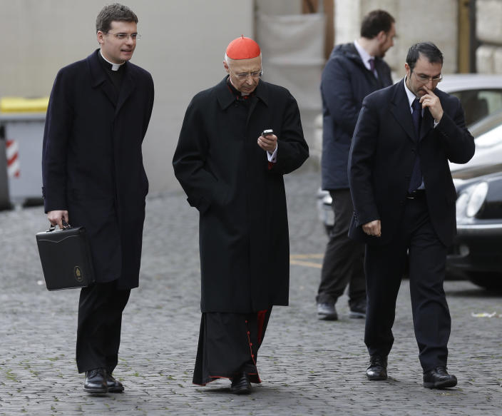 Cardinal Angelo Bagnasco, center, checks his mobile phone as he arrives for a meeting at the Vatican, Friday, March 8, 2013. The last cardinal who will participate in the conclave to elect the next pope arrived in Rome on Thursday, meaning a date can now be set for the election. One U.S. cardinal said a decision on the start date is expected soon. (AP Photo/Alessandra Tarantino)