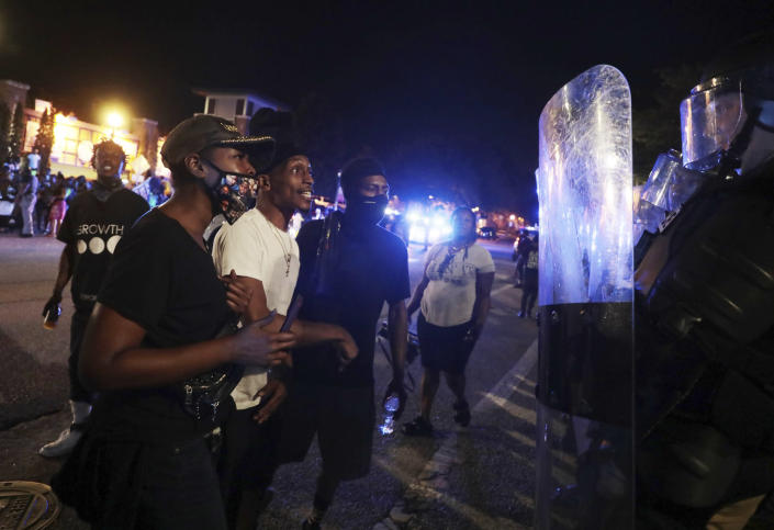 Protesters confront police officers in riot gear on Thursday night, June 24, 2021 in downtown Rock Hill, S.C. Police arrested 11 people on Thursday night as Rock Hill protest continues against controversial police arrest(Tracy Kimball/The Charlotte Observer via AP)