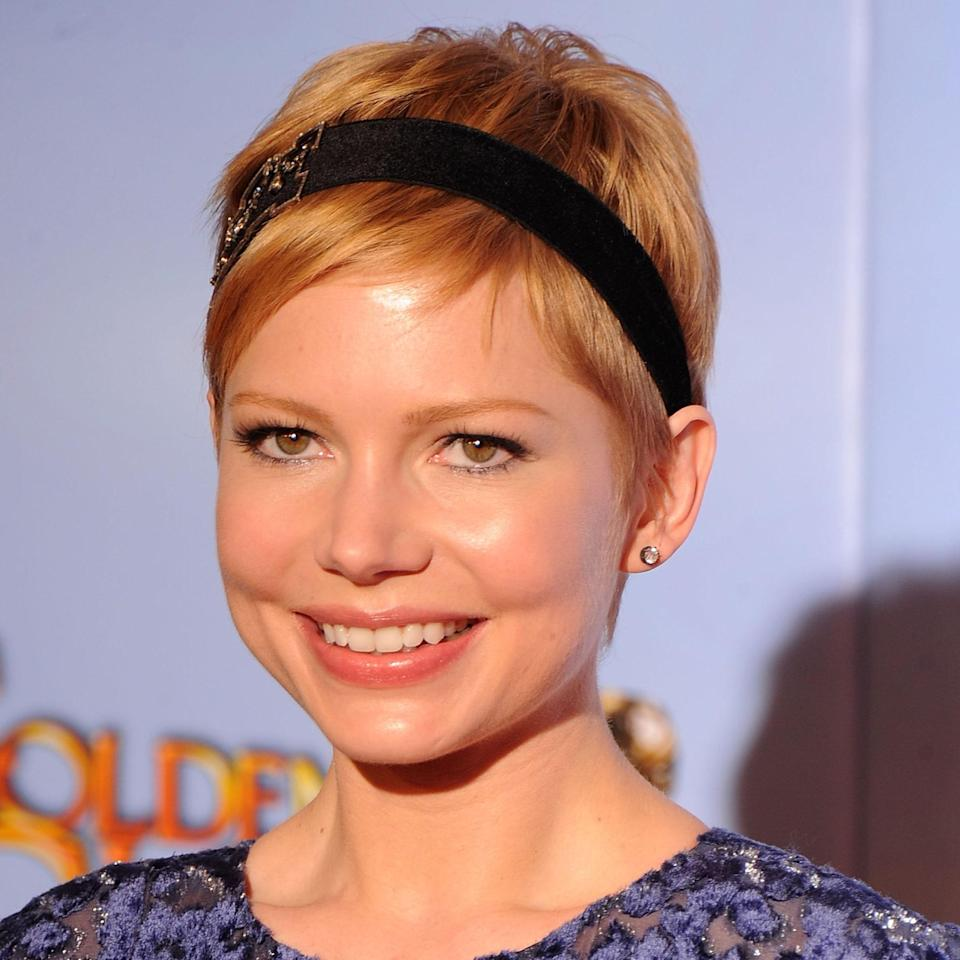 """Michelle Williams's pixie has a feminine feel with its soft ends and the addition of an ornate headband. Adams says to consider a piece that shows off your shoulders, back, décolleté, and/or neck if you're wearing this hairstyle. The super short length of the hair emphasizes rather than competes with those features.<br> <br> To style, Adams recommends applying <a href=""""https://www.allure.com/story/5-mousses-for-under-10-every-hairstyle?mbid=synd_yahoo_rss"""" rel=""""nofollow noopener"""" target=""""_blank"""" data-ylk=""""slk:mousse"""" class=""""link rapid-noclick-resp"""">mousse</a> to damp hair and blow-drying to add volume. Use a small <a href=""""https://www.allure.com/gallery/best-flatirons-for-every-budget?mbid=synd_yahoo_rss"""" rel=""""nofollow noopener"""" target=""""_blank"""" data-ylk=""""slk:flatiron"""" class=""""link rapid-noclick-resp"""">flatiron</a> to piece out the fringe and section in front of the ear. Finish with a light <a href=""""https://www.allure.com/gallery/best-hair-spray?mbid=synd_yahoo_rss"""" rel=""""nofollow noopener"""" target=""""_blank"""" data-ylk=""""slk:hairspray"""" class=""""link rapid-noclick-resp"""">hairspray</a> that has shine to it. Just don't go overboard with any type of mattifying product — that would bring the look from feeling fancy to more casual."""