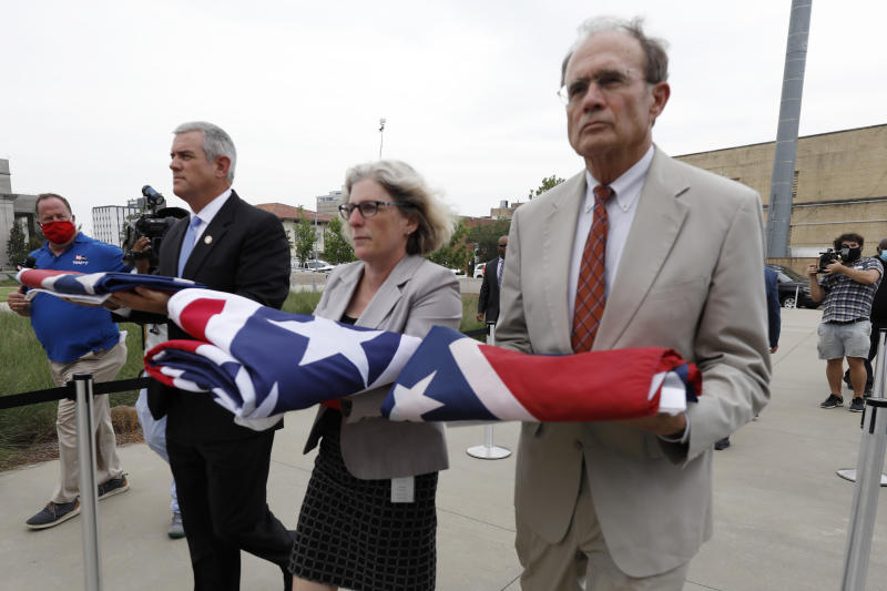 Speaker Philip Gunn, R-Clinton, left, Lt. Gov. Delbert Hosemann, right, and Mississippi Department of Archives and History Director Katherine Blount, center, carry the former Mississippi state flags to the Two Mississippi Museums during its retirement ceremony in Jackson, Miss., Wednesday, July 1, 2020. The flags had flown over the Capitol grounds during the day. The banner was the last state flag with the Confederate battle emblem on it. (AP Photo/Rogelio V. Solis)