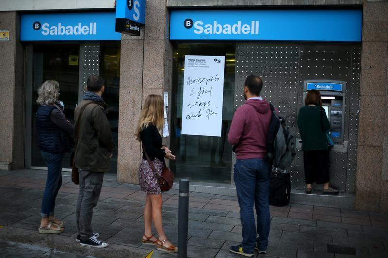 FILE PHOTO: People line up at a Sabadell Bank ATM machine in Barcelona to withdraw money as part of an action to protest the transfer of the bank's headquarters out of Barcelona