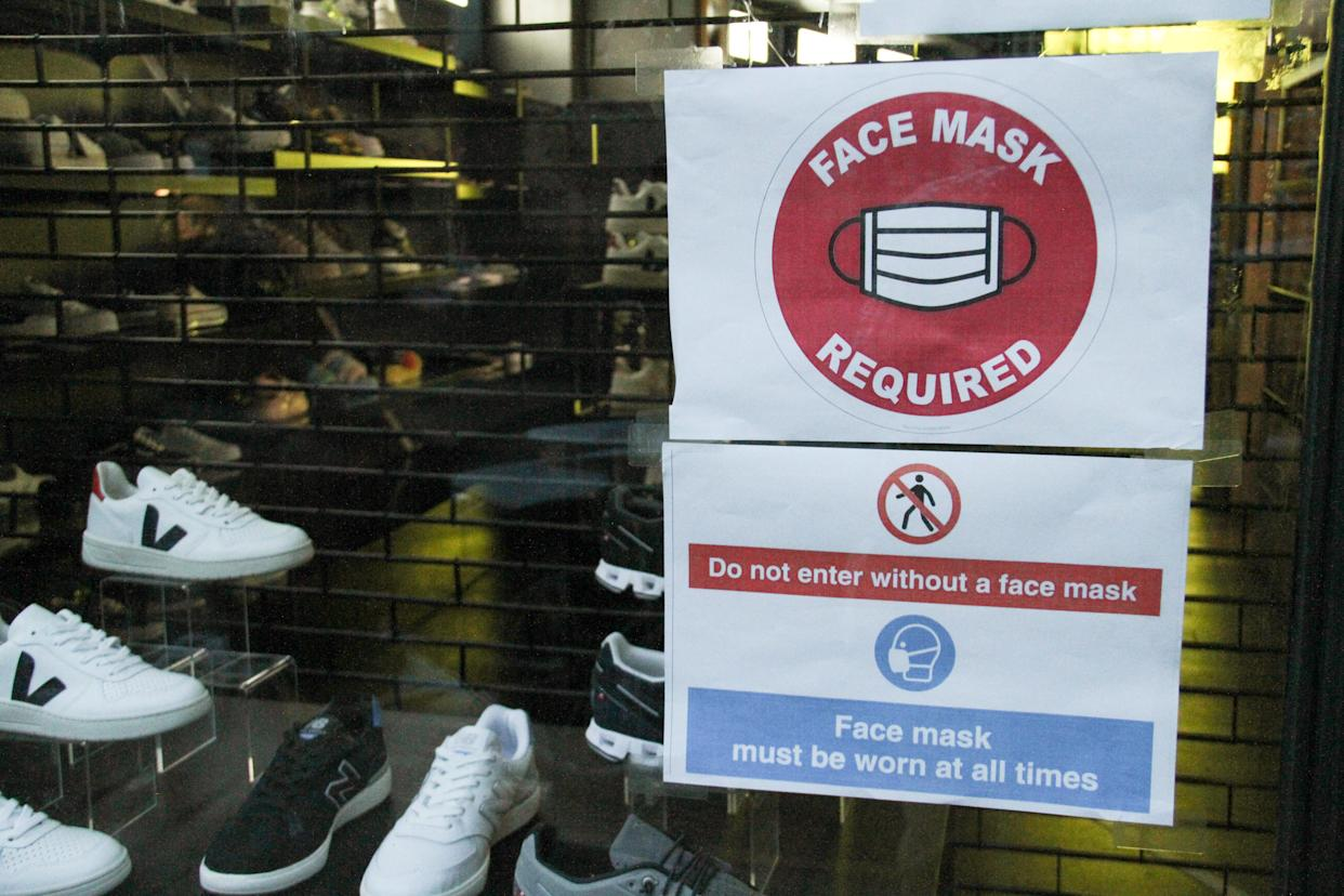 A sign outside a shop in Bricklane reminds customers to wear a face mask. The Government has made it mandatory to wear face coverings in all public transport, supermarkets and indoor shopping centers as a measure to combat the spread of the novel coronavirus. (Photo by David Mbiyu / SOPA Images/Sipa USA)