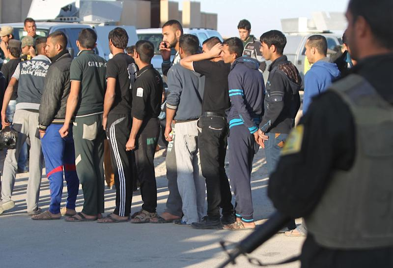 Iraqi Sunni volunteers stand in line at the Al-Asad air base in Anbar province on November 11, 2014, before they begin training by Iraqi forces to fight against Islamic State group