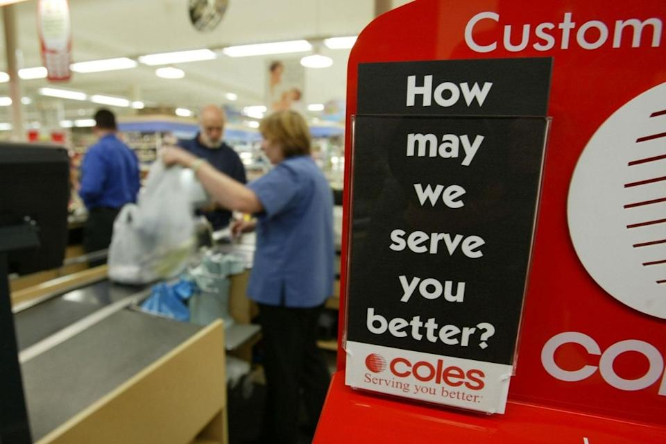 Coles staffer serves customer at checkout. Source: Getty Images
