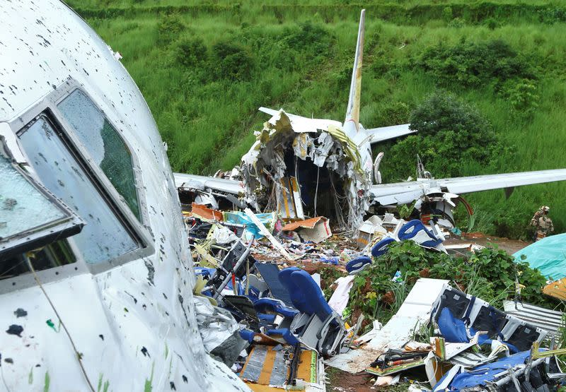 A security official inspects the site where a passenger plane crashed when it overshot the runway at the Calicut International Airport in Karipur