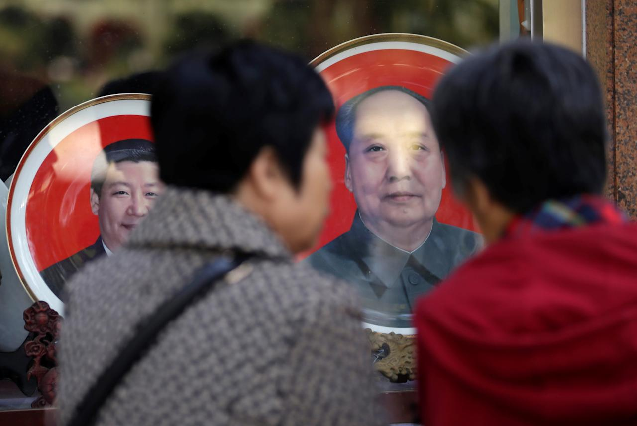 Tourists look at souvenir plates with images of Chinese late Chairman Mao Zedong (R) and Chinese President Xi Jinping outside a shop next to Tiananmen Square during the ongoing 19th National Congress of the Communist Party of China, in Beijing, China October 23, 2017. REUTERS/Jason Lee