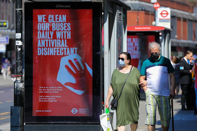 A couple wearing face masks as a preventive measure walk past 'We Clean Our Buses Daily With Antiviral Disinfectant' a Transport for London's digital COVID-19 campaign, in London. (Photo by Dinendra Haria / SOPA Images/Sipa USA)