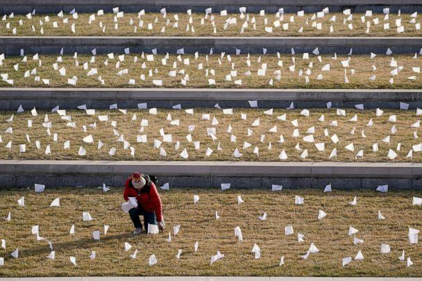 PHOTO: A man places flags at the National World War I Museum and Memorial, Jan. 19, 2021, in Kansas City, Mo. (Charlie Riedel/AP, FILE)