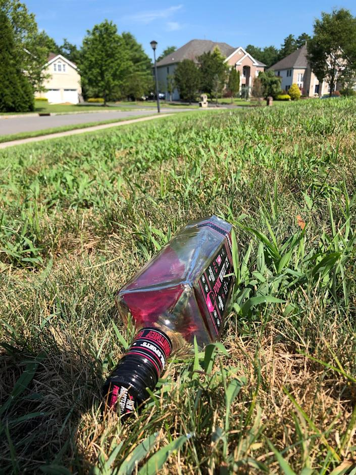 A liquor bottle in the grass in the neighborhood where a large party was held in Jackson, New Jersey, Sunday night.