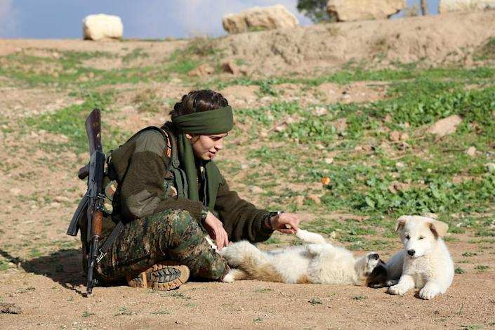 """Syriac Christian Lucia, member of the battalion called the """"Female Protection Forces of the Land Between the Two Rivers"""" plays with puppies during training on December 1, 2015 at their camp in the town of al-Qahtaniyah (AFP Photo/Delil Souleiman)"""