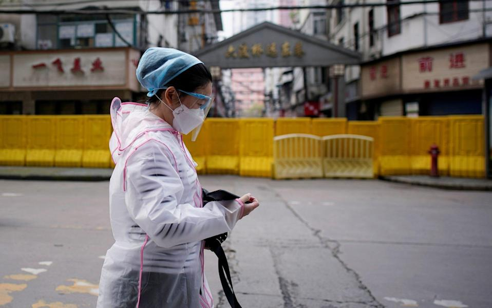 A woman wearing a face mask walks at a residential area blocked by barriers in Wuhan, the city where the coronavirus outbreak began - Aly Song/Reuters