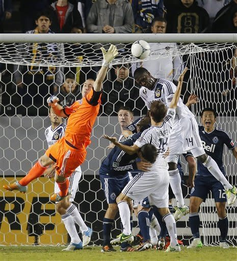 Los Angeles Galaxy's Edson Buddle, top left, attempts to score against Vancouver Whitecaps goalkeeper Brad Knighton, left, in the first half of an MLS playoff soccer match in Carson, Calif., Thursday, Nov. 1, 2012. (AP Photo/Jae C. Hong)