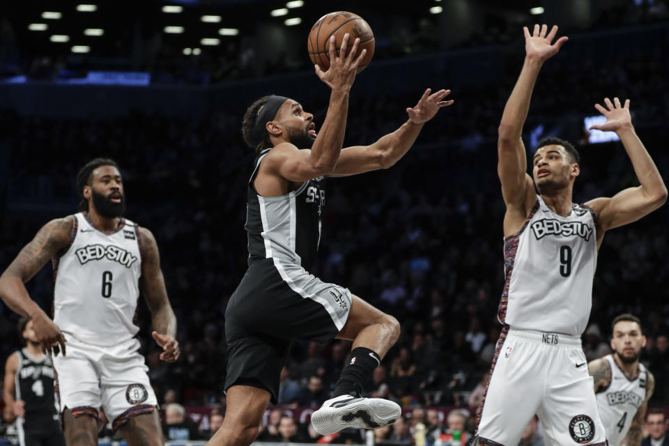 San Antonio Spurs' Patty Mills, center, drives past Brooklyn Nets' DeAndre Jordan, left, and Timothe Luwawu-Cabarrot during the first half of an NBA basketball game Friday, March 6, 2020, in New York. (AP Photo/Frank Franklin II)