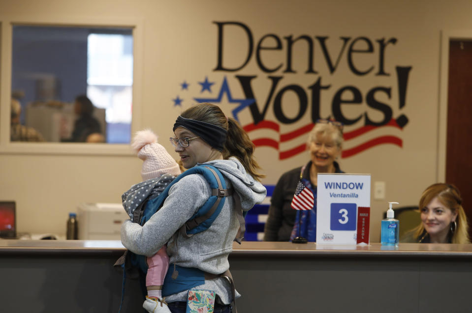 A voter holds her baby while seeking help from election judges in the lobby of the Denver Elections Division early Tuesday, Nov. 5, 2019, in Denver. (AP Photo/David Zalubowski)