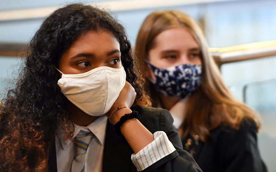 Pupils wear face masks as they sit in class at Springburn Academy school in Glasgow - AFP