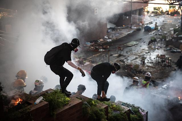 Anti-government protesters walk past a fire during clashes with police at Hong Kong Polytechnic University on Nov. 18, 2019 in Hong Kong, China. (Photo: Laurel Chor/Getty Images)