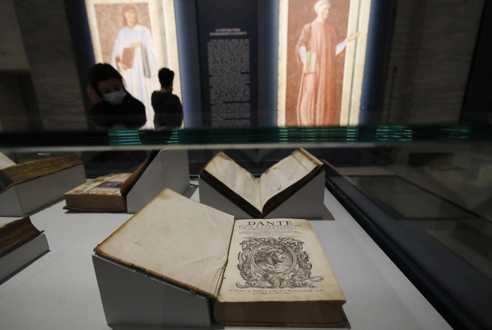 """A woman looks at ancient books displayed at the """"Dante. La visione dell'arte"""" (Dante. The Vision of Art) exhibition, in Forli, Italy, Saturday, May 8, 2021. Italy is honoring its great poet Dante Alighieri in myriad ways on the 700th anniversary of his death, with new musical scores and gala concerts, exhibits and dramatic readings against stunning backgrounds in every corner of the land. (AP Photo/Antonio Calanni)"""