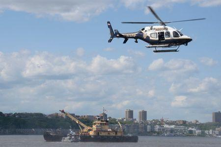 A New York City Police (NYPD) helicopter flies over the site of a helicopter that crashed into the Hudson River is lifted on to the deck of an Army Corp of Engineers boat in New York City, U.S., May 15, 2019.  REUTERS/Jefferson Siegel