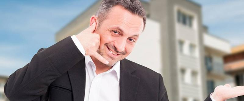Cheerful realtor holding something in palm and doing call gesture