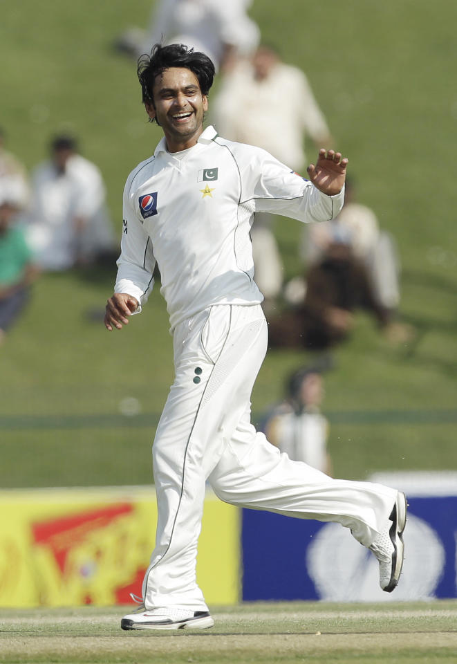 Pakistan's Mohammad Hafeez celebrates taking the wicket of England's Alastair Cook during the fourth day of the second cricket Test match of a three match series between England and Pakistan at Zayed Cricket Stadium in Abu Dhabi, United Arab Emirates, Saturday, Jan. 28, 2012. (AP Photo/Hassan Ammar)