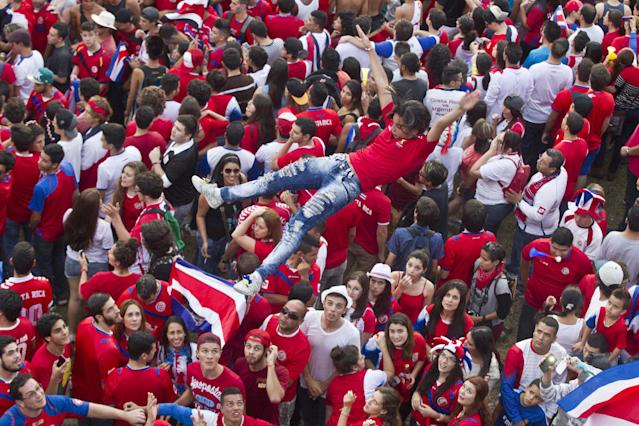 Costa Rica soccer fans throw a woman in the air as they celebrate their team's victory over Greece at a Brazil World Cup round of 16 game in San Jose, Costa Rica, Sunday, June 29, 2014. Costa Rica won a penalty shootout 5-3 after the match ended 1-1 following extra time. (AP Photo/Esteban Felix)