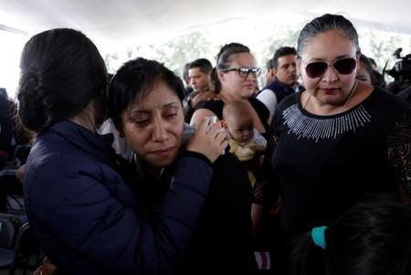 Relatives of a police officer, who was killed along other fellow police officers during an ambush by suspected cartel hitmen, react during an homage organised by the state government, in Morelia