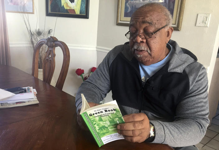 """In this Jan. 31, 2019 photo, Charles Becknell, Sr., holds a copy of the 1954 edition of """"The Negro Motorist Green Book"""" at his home in Rio Rancho, N.M. Becknell, of Rio Rancho, New Mexico, grew up in segregated Hobbs and recalls entering some restaurants with his family from the back because only whites could enter from the front. He also attended sit-ins at restaurants where blacks were not allowed at all. """"Even our high school football games had segregated seating,"""" recalled Becknell, who said close friends of differing races would sit on each side of a dividing rope on the bleachers so they could watch a game together. (AP Photo/Russell Contreras)"""