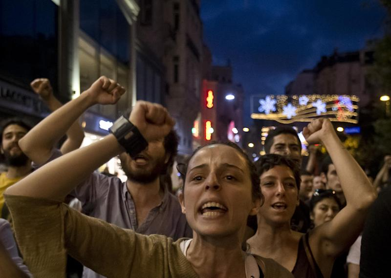 People chant slogans in Istiklal Avenue as they try to reach Taksim Square and Gezi Park, Istanbul, Turkey, Tuesday, July 9, 2013. Gezi Park remained open for the night after thousands of anti-government protesters broke their fast for the holy month of Ramadan by sitting down for a meal along a main Istanbul pedestrian street for a makeshift Ramadan banquet that stretched some 500 meters (yards) toward the city's landmark Taksim Square. (AP Photo/Vadim Ghirda)