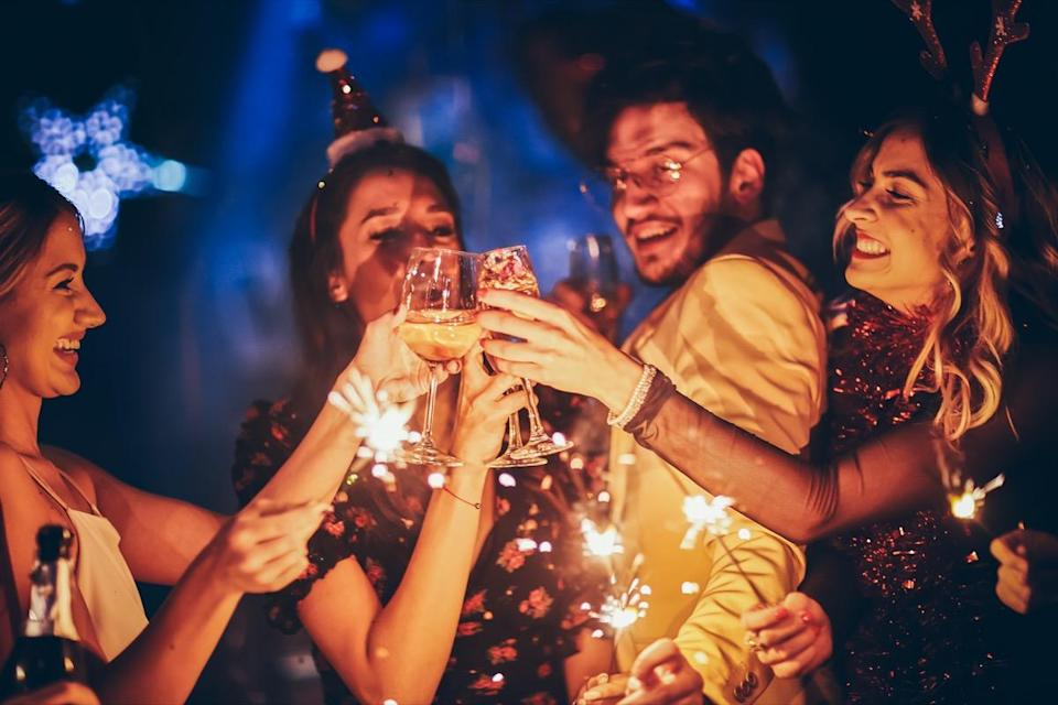 Group of friends having fun and holding sparklers at New Year's party