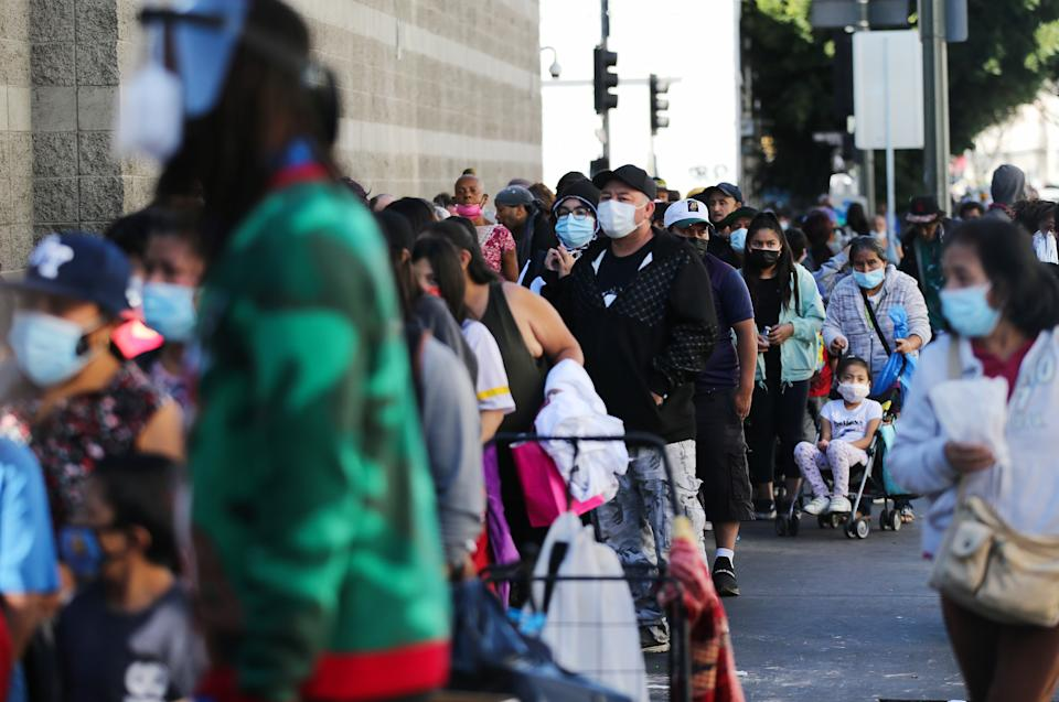 LOS ANGELES, CALIFORNIA - DECEMBER 25: Community members wait in line to receive holiday-themed takeout meals and backpacks with toiletries from the Midnight Mission in Skid Row on Christmas day amid the COVID-19 pandemic on December 25, 2020 in Los Angeles, California.  California has become the first state to hit 2 million COVID-19 cases. Southern California remains at zero percent of its ICU (Intensive Care Unit) available bed capacity amid a spike in coronavirus cases and hospitalizations. (Photo by Mario Tama/Getty Images)