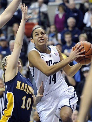 Connecticut's Bria Hartley, right, drives past Marquette's Brooklyn Pumroy during the first half of an NCAA college basketball game in Storrs, Conn., Tuesday, Feb. 5, 2013. (AP Photo/Fred Beckham)