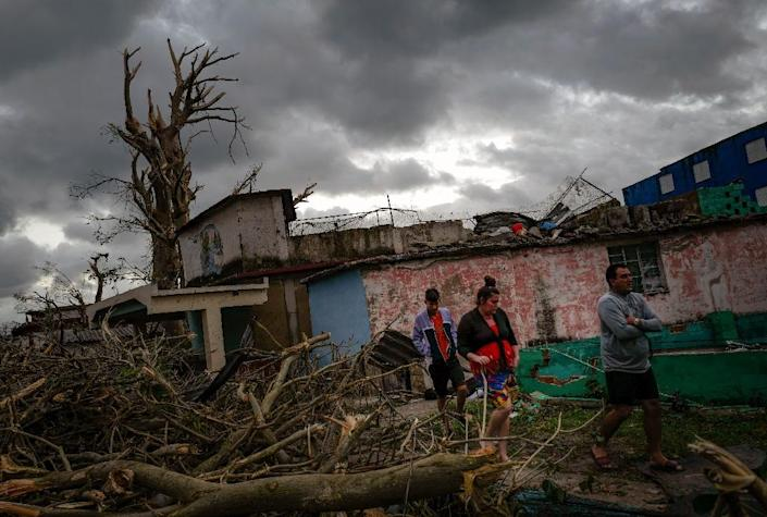 Residents of tornado-hit Regla neighborhood walk amid the debris, in Havana, on January 28, 2019 after a rare and powerful tornado struck (AFP Photo/ADALBERTO ROQUE)