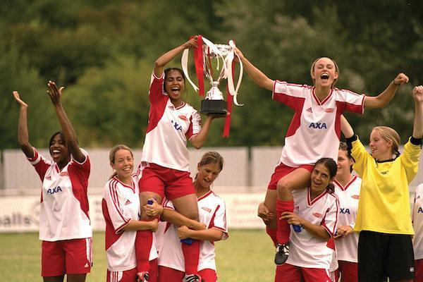 Parminder Nagra and Keira Knightley being hoisted up by their teammates as they hold a trophy.