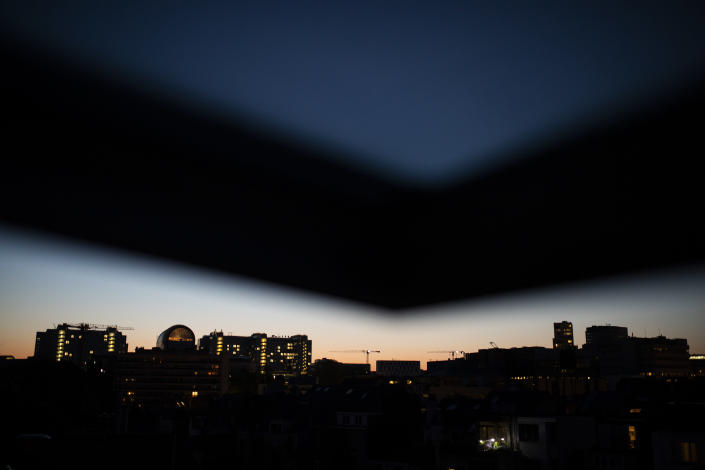 The European Parliament building, left, is silhouetted against the sky as the sun sets during a partial lockdown against the spread of the coronavirus or COVID-19 in Brussels, Monday, April 20, 2020. (AP Photo/Francisco Seco)