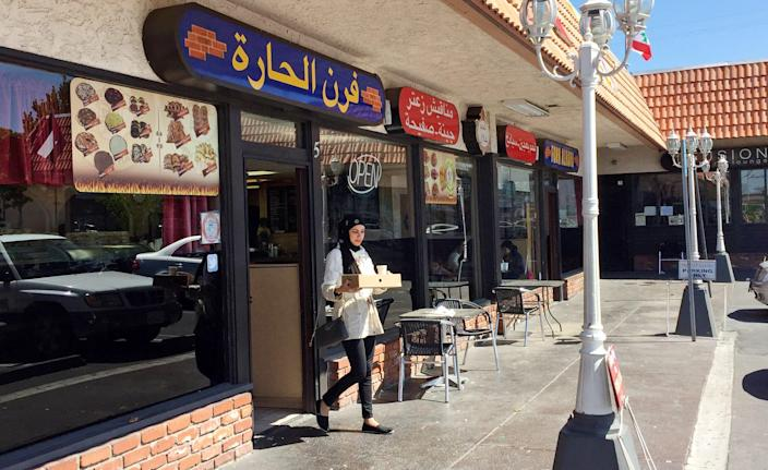 """A customer exits a Lebanese eatery in Anaheim's """"Little Arabia"""" neighborhood just miles from Disneyland in Orange County. Southern California is home to the nation's largest concentration of Arab Americans."""
