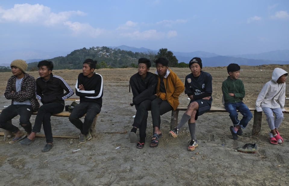 "A.S. Ngayaomi, 20, third right, who is sitting in as a substitute player, watches a friendly football match between villages in Shangshak, with Nungshang village seen in the background mountaintop, in Shangshak village, in the northeastern Indian state of Manipur, Saturday, Jan. 30 2021. ""We learn to play the game from the time we start walking,"" Ngayaomi said. (AP Photo/Yirmiyan Arthur)"