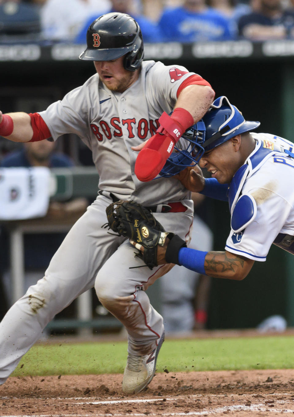 Boston Red Sox's Christian Arroyo, left, is tagged out at home by Kansas City Royals catcher Salvador Perez during the third inning of a baseball game in Kansas City, Mo., Friday, June 18, 2021. (AP Photo/Reed Hoffmann)