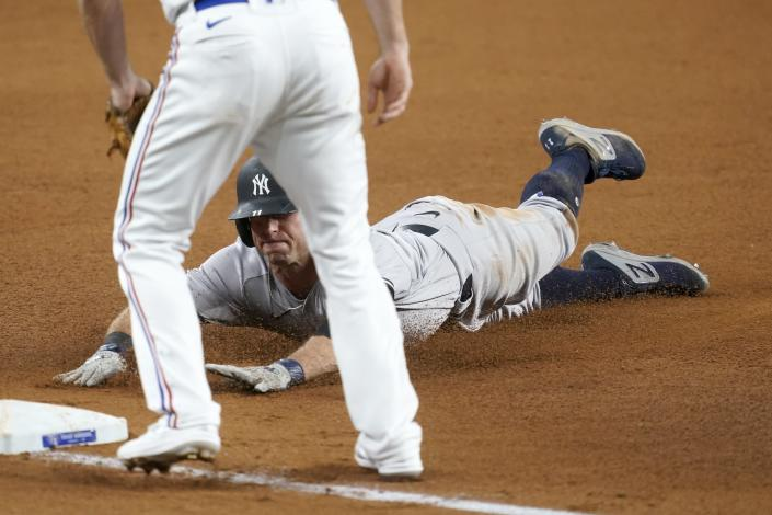 Texas Rangers shortstop Charlie Culberson, front, stands by the bag as New York Yankees' Brett Gardner slides safely into it with a triple in the fourth inning of a baseball game in Arlington, Texas, Monday, May 17, 2021. (AP Photo/Tony Gutierrez)