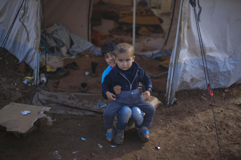 Two Syrian boys who fled with their family from the violence in their village, sit in front of a tent at a displaced camp, in the Syrian village of Atma, near the Turkish border with Syria. Saturday, Nov. 10, 2012. (AP Photo/ Khalil Hamra)