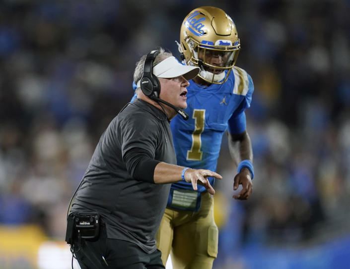 UCLA head coach Chip Kelly stands next to quarterback Dorian Thompson-Robinson during the second half of an NCAA college football game against Fresno State on Saturday, Sept. 18, 2021, in Pasadena, Calif. If anyone symbolizes the rollercoaster that has been UCLA football during the Chip Kelly era it is quarterback Dorian Thompson-Robinson. (AP Photo/Marcio Jose Sanchez)