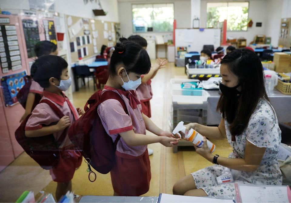 Children wearing protective face masks sanitise their hands as they attend preschool classes at St James' Church Kindergarten as schools reopen amid the coronavirus disease (COVID-19) outbreak in Singapore June 2, 2020.  REUTERS/Edgar Su