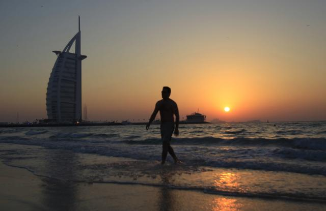 A man walks at the Palm Jumeirah beach as the Burj Al Arab hotel is seen during sunset in Dubai February 23, 2014. REUTERS/Saleh Salem (UNITED ARAB EMIRATES – Tags: SOCIETY)