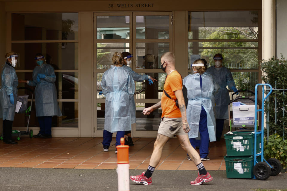 A man walks past as COVID testing Staff put on PPE before entering the Kings Park on Southbank apartment building. Source: AAP