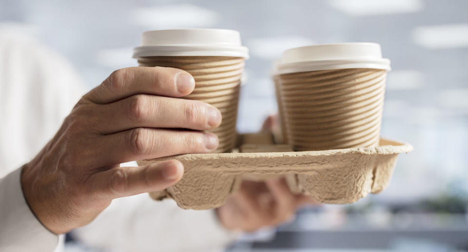 A businessman carrying take-away coffee in disposable single-use cups.