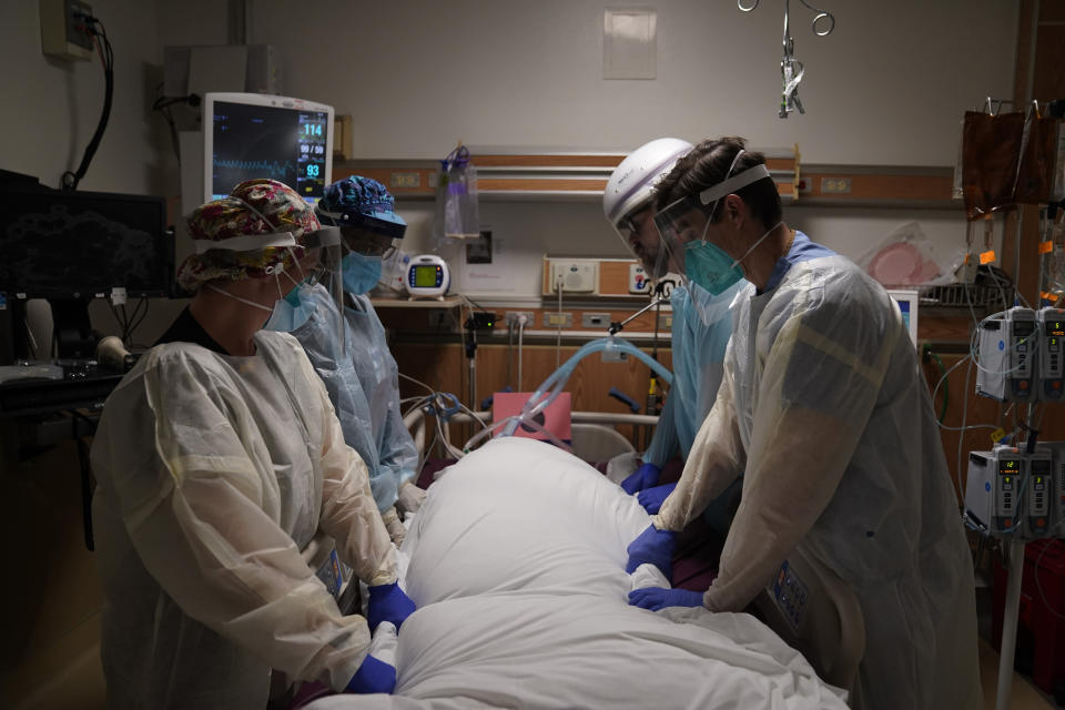 FILE - In this Dec. 22, 2020, file photo, medical workers prepare to manually prone a COVID-19 patient in an intensive care unit at Providence Holy Cross Medical Center in the Mission Hills section of Los Angeles. California surpassed 25,000 coronavirus deaths since the start of the pandemic, reporting the grim milestone Thursday, Dec. 31, 2020, as it continues to face a surge that has swamped hospitals and pushed nurses and doctors to the breaking point as they brace for an anticipated surge after the holidays. (AP Photo/Jae C. Hong, File)