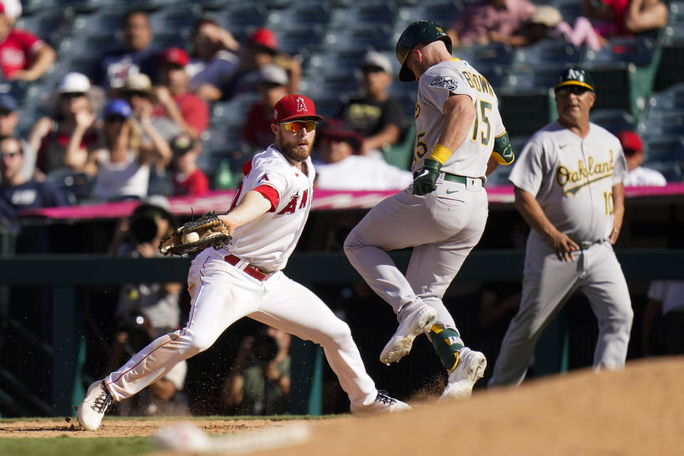 Oakland Athletics' Seth Brown, center, safely takes first base as Los Angeles Angels first baseman Jared Walsh, left, fields a throw during the 10th inning of a baseball game Sunday, Sept. 19, 2021, in Anaheim, Calif. (AP Photo/Jae C. Hong)