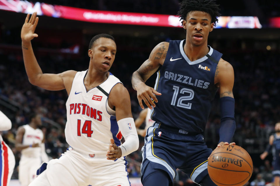 Memphis Grizzlies guard Ja Morant (12) controls the ball as Detroit Pistons forward Louis King (14) defends during the first half of an NBA basketball game, Friday, Jan. 24, 2020, in Detroit. (AP Photo/Carlos Osorio)