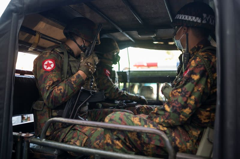 Myanmar soldiers sit inside a vehicle as they guard in front of a Hindu temple in the downtown area in Yangon